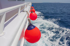 View down the side of a private motor boat. View down the side of a private motor yacht traveling on tropical ocean with fenders Stock Photo