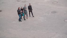 View down on the street where four young stylish people walk. Two girls and two men have a walk. Slow mo, steadicam shot. View down on the street where four stock footage