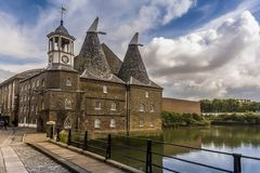 A view down Three Mill Lane in Lee Valley, London. A view down Three Mill Lane towards the Clock Mill, part of the oldest tidal mills complex in the world in Lee royalty free stock photo