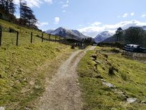 View down track and farm to distant mountains Royalty Free Stock Photos