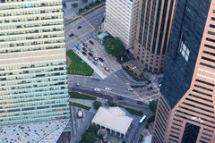 View downwards to the streets between skyscrapers in Singapore. View downwards to the streets with cars between skyscrapers in Singapore Stock Photo