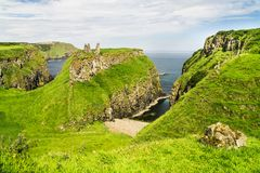 View of the dramatic coastal scenery on the coast of County Antrim, Northern Ireland. Showing the remains of Dunseverick Castle on the top of a coastal inlet royalty free stock images