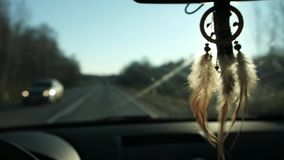 View of dream catcher hanging from rearview mirror inside car. Travel by car. View of the road and snowy mountains in. The evening stock video