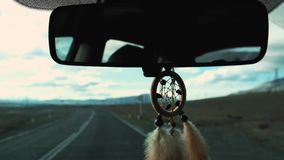 View Of Dream Catcher Hanging From Rearview Mirror Inside Car. Travel by car. View of the road and snowy mountains in. The evening stock footage