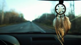 View of dream catcher hanging from rearview mirror inside car. Travel by car. View of the road and snowy mountains in. The evening stock video footage