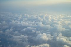 View of dreamy fluffy abstract white cloud with blue sky and sunrise light background from airplane window Stock Photo