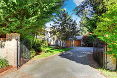 View of driveway with opened gate. Double garage and well kept garde Stock Images