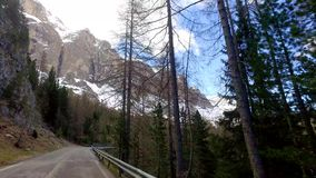 View from a driving car on the winding roads in the mountains, Dolomites, Alps stock video footage