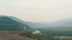 View from drone on the charming woman raising up hands while standing on the edge of the mountains. View from drone on the charming woman raising up hands while stock video footage