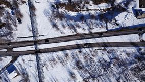 The view from the drone. Gray road with cars. Around snow white, trees and bushes. Two lines on a white background. Drone footage royalty free stock photography