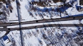 The view from the drone. Gray road with cars. Around snow white, trees and bushes. Two lines on a white background. Drone footage royalty free stock photos