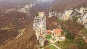 View from drone of small monastery complex with chapel on top of high rock formation of Katskhi Pillar in Imereti region