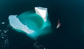 Iceberg and yacht. View from air. Drones view. stock photos