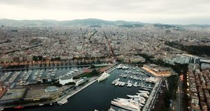 View from drones of sailboats and yachts in old port of Barcelona. And gothic quarter at evening stock footage