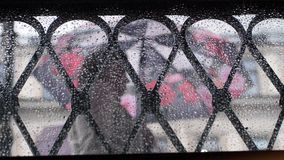 View from the droplets window on blurred people walking with umbrellas during rain. View from the droplets window on people walking with umbrellas during rain Royalty Free Stock Photo