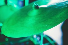 View of drum set kit on a stage during rock show performance, with band performing in the background, drummer point of view. Concert Stock Photo