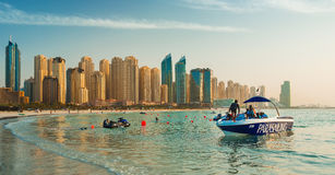 View on Dubai Marina and Jumeirah beach,where people are relaxing and parasailing at the sunset Stock Images