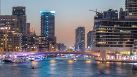 View of Dubai Marina Towers and canal in Dubai day to night timelapse. Vew of Dubai Marina embankment with Towers and yachts from bridge in Dubai day to night stock video