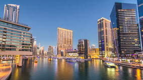 View of Dubai Marina Towers and canal in Dubai day to night timelapse. Vew of Dubai Marina embankment with yachts and modern Towers near mall from bridge in stock video