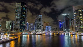 View of Dubai Marina Towers and canal in Dubai night timelapse hyperlapse. Vew of Dubai Marina promenade with yachts and modern Towers reflected in water from stock video footage