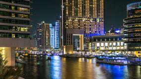 View of Dubai Marina Towers and canal in Dubai night timelapse. Vew of Dubai Marina embankment with yachts and modern Towers from bridge in Dubai night timelapse stock video footage