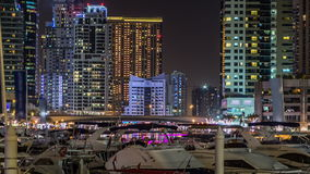 View of Dubai Marina Towers and canal in Dubai night timelapse. Vew of Dubai Marina with yachts and modern Towers from promenade in Dubai night timelapse, United stock video footage