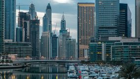 View of Dubai Marina Towers and canal in Dubai night to day timelapse. Vew of Dubai Marina embankment with Towers and yachts from bridge in Dubai night to day stock footage