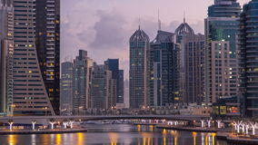 View of Dubai Marina Towers and canal in Dubai night to day timelapse. Vew of Dubai Marina canal, embankment with modern Towers and yachts reflected in water stock video