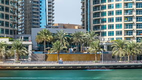 View of Dubai Marina Towers and waterfall in Dubai timelapse hyperlapse. Vew of Dubai Marina promenade with waterfall, palms and modern Towers reflected in green stock video footage