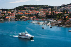View on Dubrovnik, Croatia. View from the sea on Duvrovnik in Coratia with houses with red roofs, a white boat and hills with green vegetation Royalty Free Stock Photography