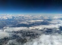 View of the earth from high altitude with dark blue sky and different types of white clouds with snow on a hilly landscape. Aerial view of the earth from high royalty free stock photo