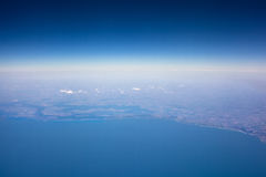 View of Earth from plane, blue sky and the sea. View from the plane, the blue sky and the sea, land a top view Royalty Free Stock Photo