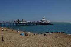 View of Eastbourne pier from the shingle beach. Senic photo of people enjoying the summer afternoon on the beach with the pier royalty free stock photo