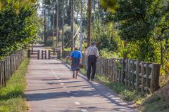 View of eco pedestrian / cycle lane, with couple of senior farmers, walking and carrying agricultural tools royalty free stock images