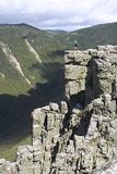 View from the edge. A hiker stops to enjoy the view from the edge of a cliff in the white mountains stock photography