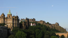 View of Edinburgh and Castle. Morning view of Castle and other buildings in Edinburgh, Scotland with moon visible in top-right corner Stock Photography