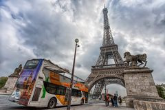View of Eiffel Tower in a day of a cloudy sky from Pont d`Iena with a tourist bus in Paris, France royalty free stock photo