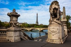 View of the Eiffel Tower framed by statues of the Alexander III Bridge spanning the Seine River in Paris royalty free stock photos