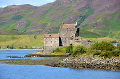 Eilean Donan Castle, Dornie, Scotland. A view of Eilean Donan Castle at Dornie, Scotland with purple heather covering the hills in the background Stock Images