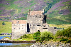 Eilean Donan Castle, Dornie, Scotland. A view of Eilean Donan Castle at Dornie, Scotland with purple heather covering the hills in the background Royalty Free Stock Photos