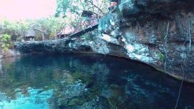 A view of the El Jardin del Eden cenote in the morning with swimmers. A view of the El Jardin del Eden cenote in the morning with swimmers stock footage