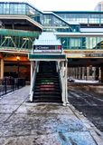 View of el train stairway and ramp to pink and green lines of Chicago`s CTA transit system, on a snowy day in winter. Clinton and Lake Street intersection Stock Image
