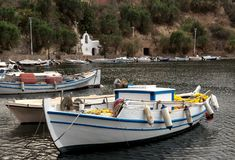 Fishing boats are near the shore. View of the embankment of the city Saint Nicholas, fishing boats and a sea lake fon a cloudy day island Crete, Greece Stock Photos