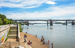 View of the embankment of the Ob river, resting people, and the. The river Ob, Novosibirsk, Siberia, Russia - July 17, 2017 October  Utilities  bridge campers Stock Photography
