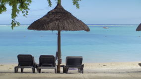 View of empty chaise-longue near native sun umbrella against blue water, Mauritius Island. View of empty chaise-longue near native sun umbrella against blue stock video