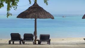 View of empty chaise-longue near native sun umbrella against blue water, Mauritius Island stock video