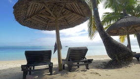View of empty chaise-longue near native sun umbrella and palm trees against blue water, Mauritius Island stock video footage