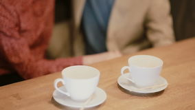 A view of empty coffee cups on the table and a couple holding hands. stock video footage