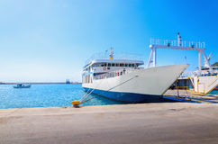 View of empty ferry in typical Greek blue white colors waiting i. N harbour to be loaded with cars Stock Photos