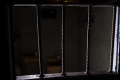 View of the empty jail cell through the bars of the doors Stock Photos